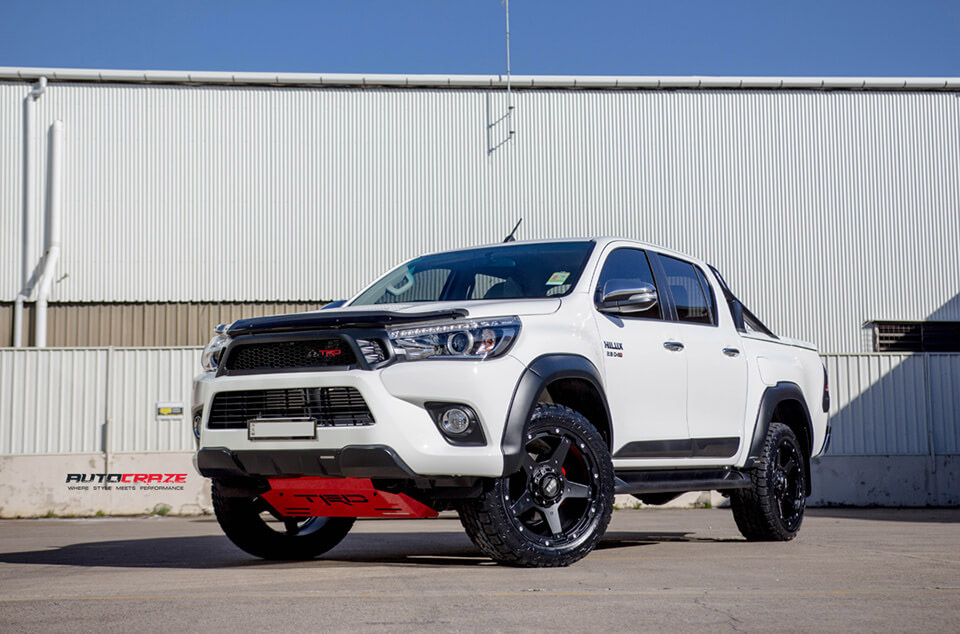 A white Toyota Hilux TRD with Grid GD04 4x4 wheels in a matte black finish. Wrapped with nitto terra grappler tyres.