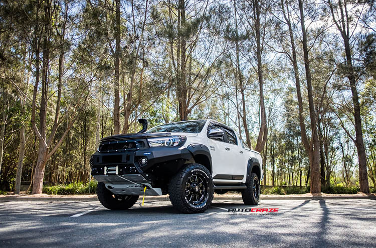 Close up shot of a Toyota Hilux with Moto Metal Wheels, wrapped in Nitto Terra Grapplers. Also includes the Rival 4X4 Drivetech Bumper Bar and Underbody Armour.