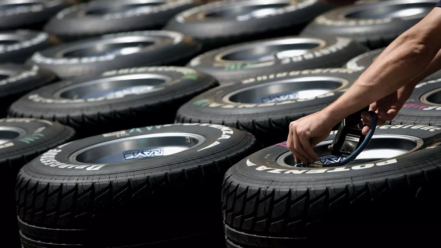 Image of someone checking the tyre pressure on tyres.